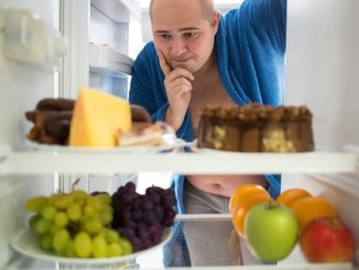 Corpulent man contemplating unhealthy food rather than healthy food. Could he be thinking if there are any trans fats in these products ?
