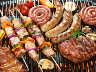 Assorted delicious grilled meat with vegetable over the coals on a barbecue.
