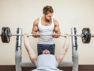 21828129 - a handsome young muscular sports man doing weight lifting and gets help from his friend.