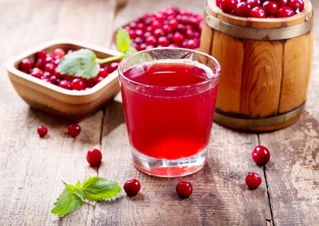 47600813 - glass of cranberry juice with fresh berries on wooden table