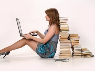 Girl with a laptop next to a pile of books. She may take huperzine.