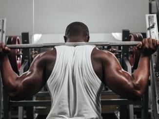 43776533 - weight training african doing bodybuilding in gym. Protein supplementation.