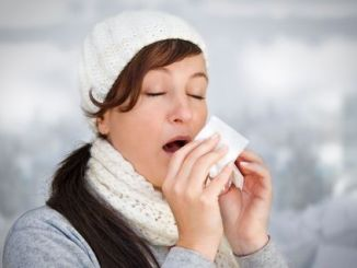 Woman with a cold holding a tissue (without snow in background). Woman taking medicine for coughs, flu and colds