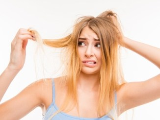 Sad girl looking at her damaged hair. Copyright: deagreez / 123RF Stock Photo