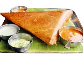 Dosa with various dressings on a pandanus leaf and all on a steel tray.