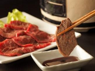 Yakiniku japanese barbecue, chopsticks picking up slices of beef.