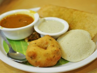 South Indian breakfast with a vada doughnut. at the front, idli and chutney.
