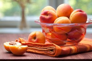 Apricots in a bowl with some cut in half.