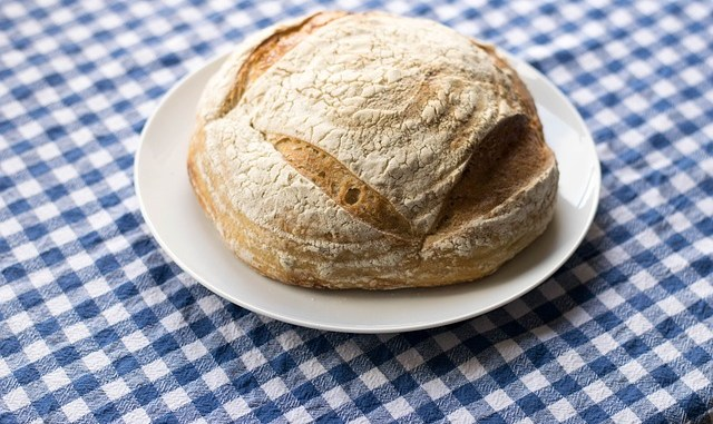 A sourdough loaf on a white plate, laid on a blue and white check tablecloth.