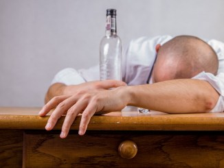 Man asleep on table with empty bottle in his grasp.