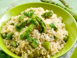 A risotto with asparagus in a pale green bowl on a green cloth with asparagus.