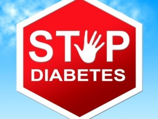 Stop sign saying stop diabetes against a blue sky.
