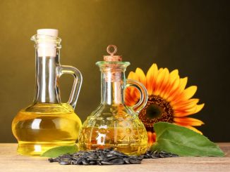 Sunflower oil and sunflower on yellow background. An example which contains PUFAs.