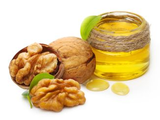 Walnut oil and nuts with leaf isolated on white background