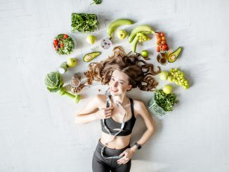 Beauty portrait of a sports woman surrounded by various healthy food lying on the floor. Healthy eating and exercise concept. Top diets 2019