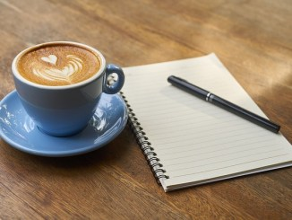 Coffee in a blue cup with saucer, a notebook and pen.