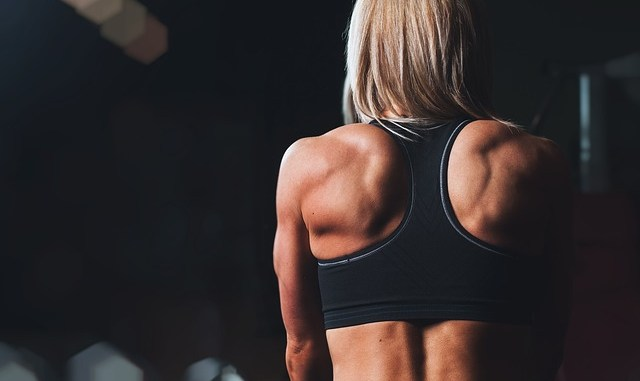 Training. A woman's back with a gym wear. DHMA is a dietary supplement which is not permitted in supplements.