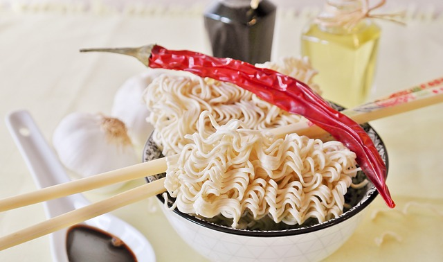 Noodles in a bowl with a red chilli pepper on top.
