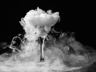 Dry ice in a champagne glass. Closeup glass with white fog at dark background. Chemical reaction of dry ice with water.
