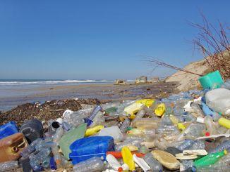 Plastic rubbish on a beach near the sea. A source of microplastics.