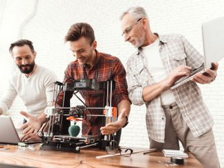 Three men are working on preparing a 3d printer for printing. Two men set up a 3d printer, an elderly man holds a laptop in his hands and watches the process. (3D Printing)