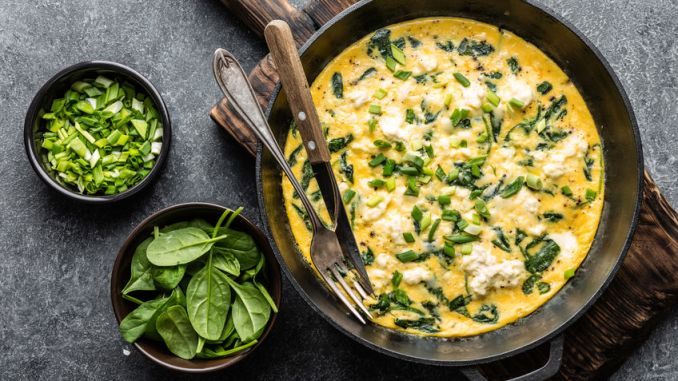 Scrambled egg omelette with spinach and cheese in a pan on the concrete background top view