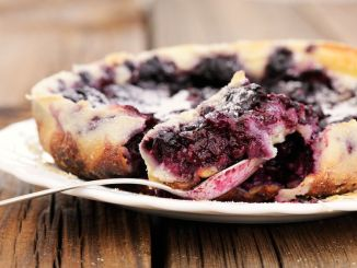 French pie clafoutis with cherry and spoon in white plate closeup