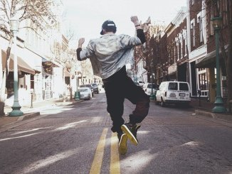 A man dancing in the street. Probably has a high testosterone level.