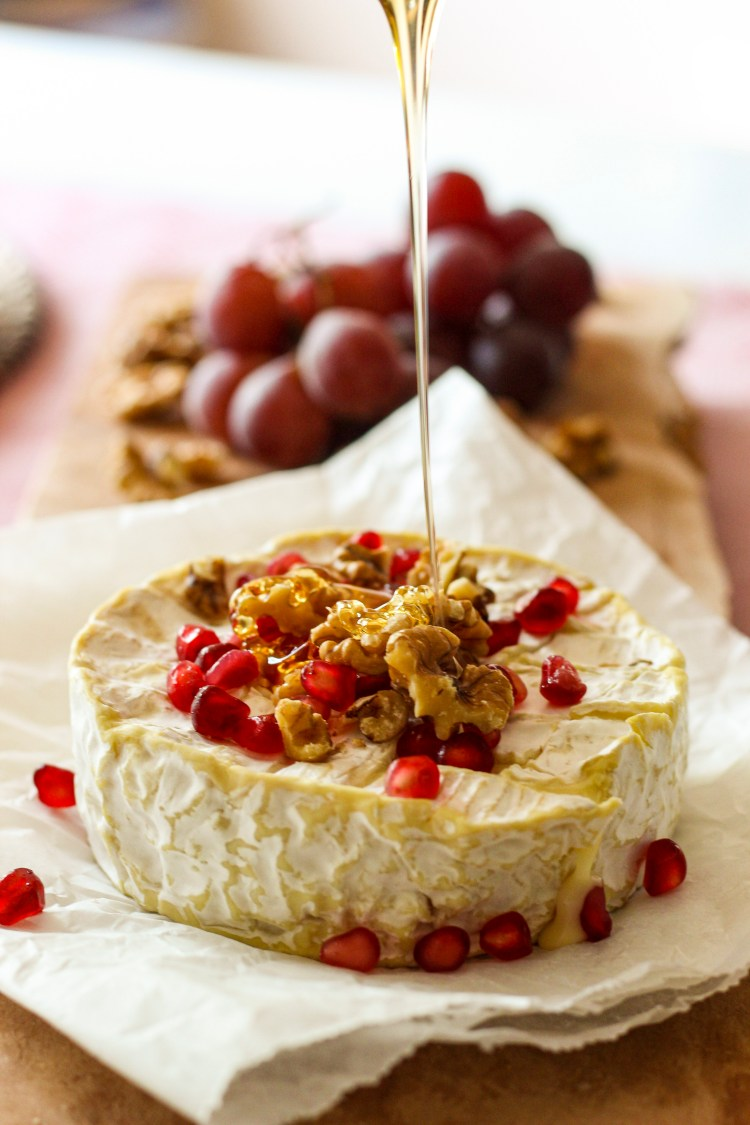 roasted brie garnished with honey , walnuts and pomenegrate