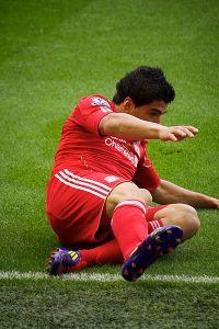 Liverpool striker Luis Suarez lying on the ground.