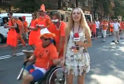 A wheelchair-bound Dutch fan tries to lift up a Ukrainian TV presenter's dress