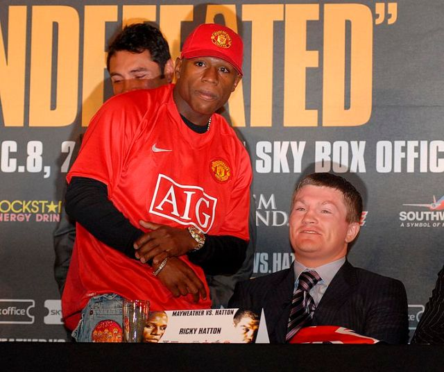 Floyd Mayweather Jr. illustrating how builders at Etihad Stadium told to remove Manchester United shirts might look