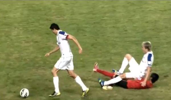 Liaoning Whowin's Zhang Jingyang tackles the wrong player from Shanghai Shenhua