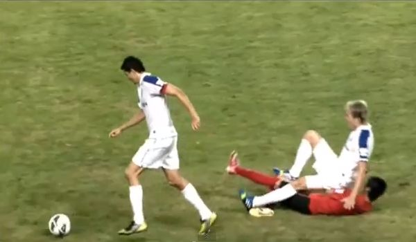 Liaoning Whowin's Zhang Jingyang tackles the wrong player from Shanghai Shenhua