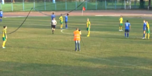 Photographer on pitch who sets up his tripod just outside the penalty area