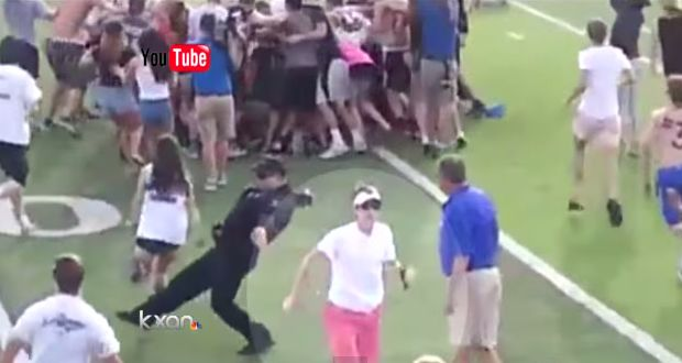Police officer trips fans during a high school pitch invasion in Austin