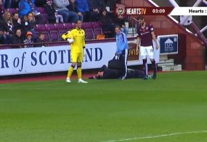An injured ball boy at Heart of Midlothian gets treatment after his slip and fall during a game against Hamilton
