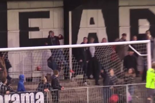 Maidenhead United fan heads ball to protect woman in stands from free kick