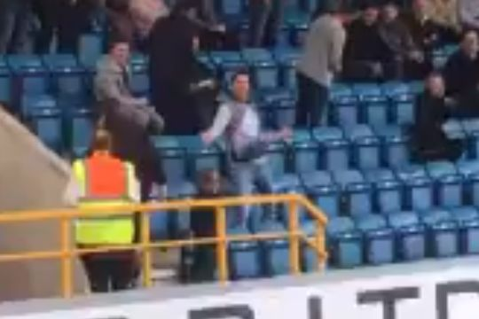 A Leeds fan dances in the stands at Millwall before their 1-0 defeat