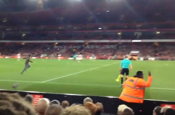 A pitch invader is chased by stewards at Arsenal vs Doncaster, League Cup 3rd round tie at the Emirates