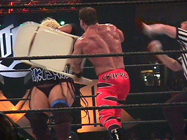 A wrestler hits another with a chair