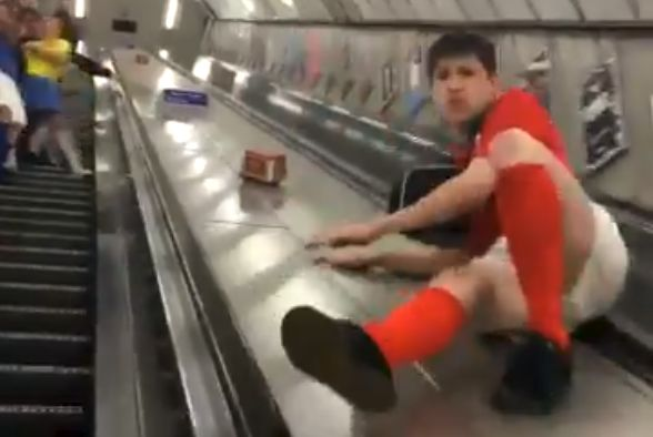 Player in full kit slides down the middle of escalators at a London Underground station and crashes into obstacles