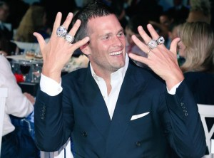 tom-brady-with-rings Eonline.com – Tom Brady @ Super Bowl Ring Ceremony for the New England Patriots in June 2015.