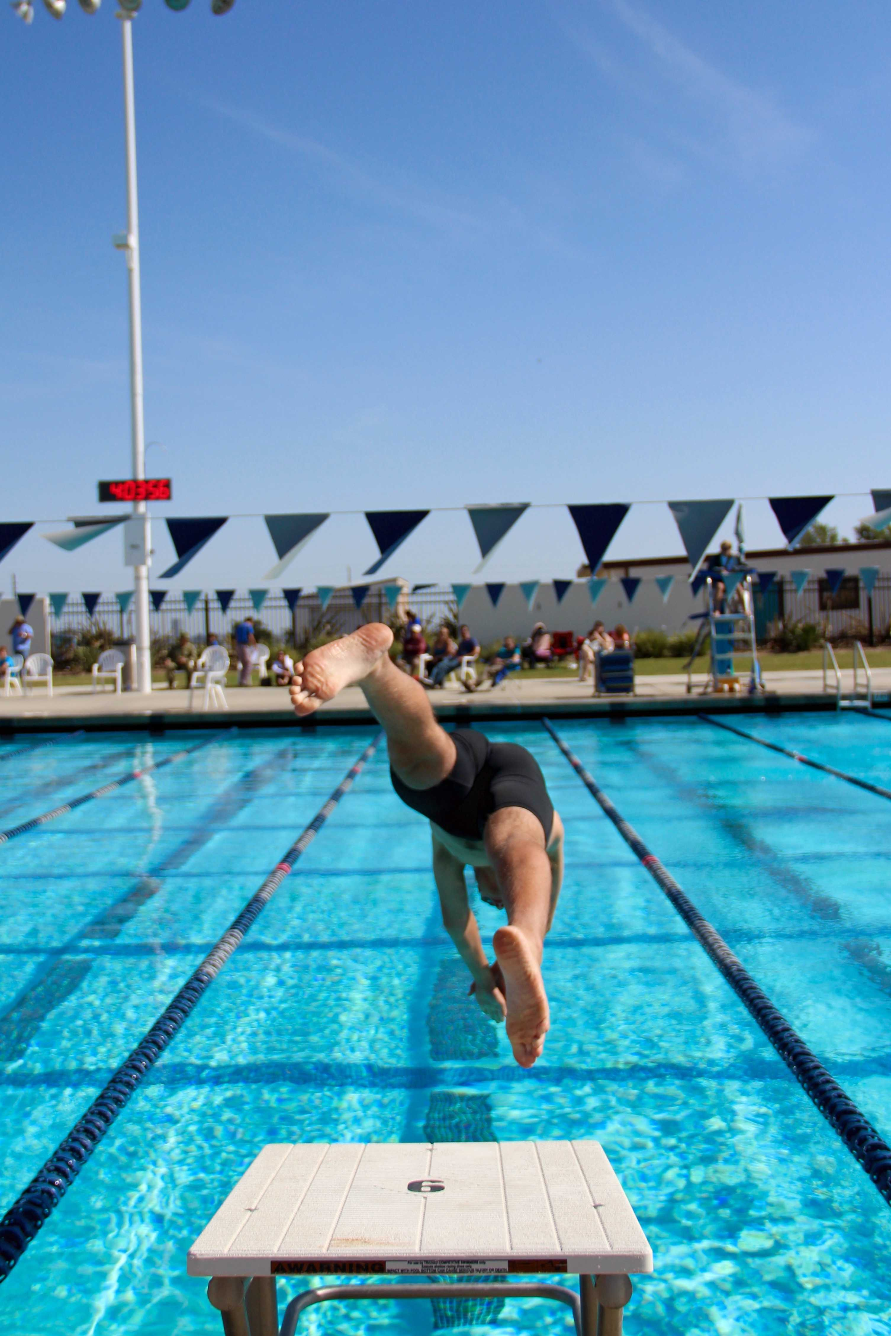A swimmer jumps into the pool, ready to compete. Credit: Kazu Koba/The Foothill Dragon Press