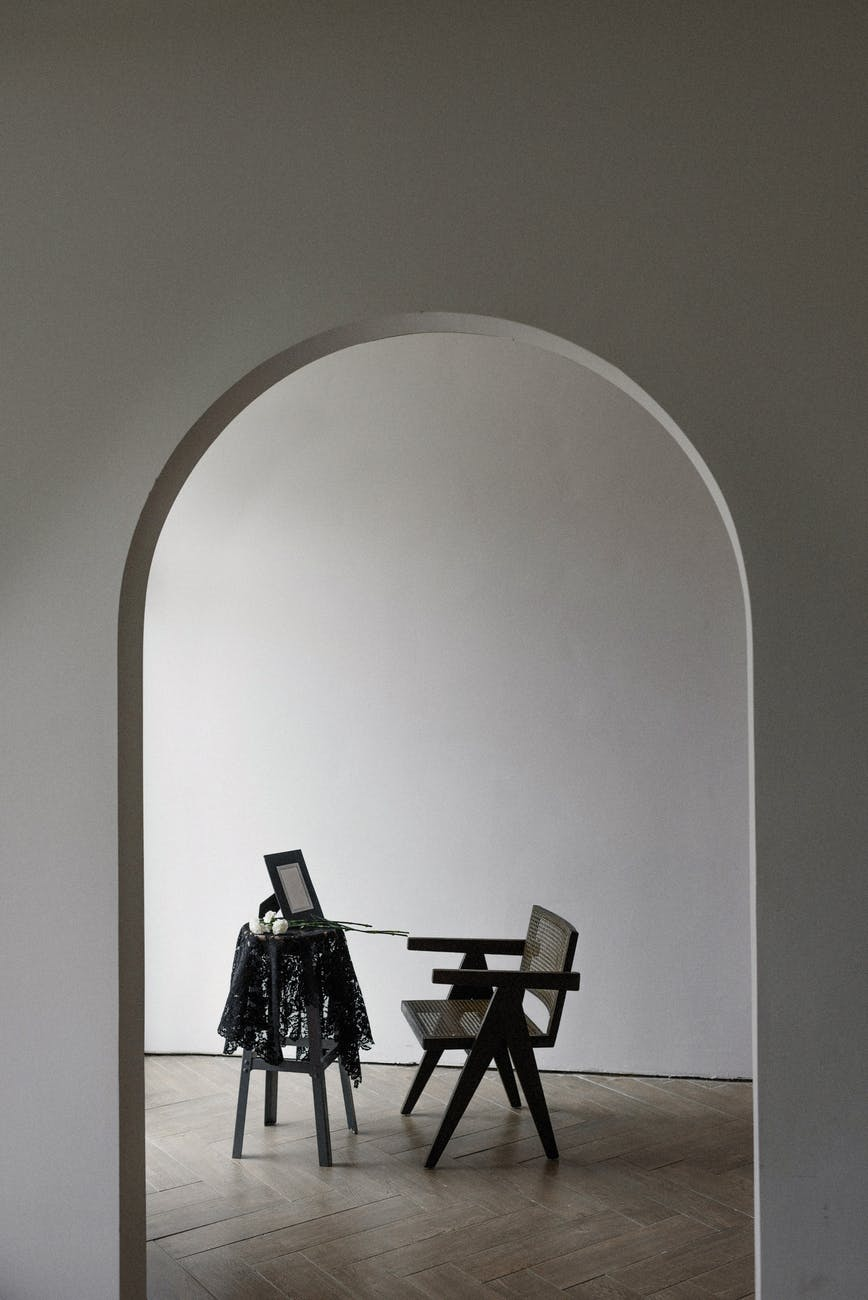 an archway towards a room with table and chair