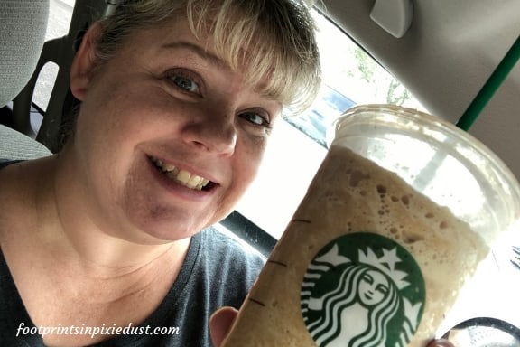 Woman smiling with her pumpkin spice coffee beverage in hand