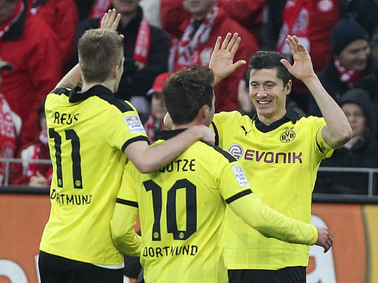 Dortmund's Robert Lewandowski (R) celebrates scoring the 2-1 with teammates during the German first division Bundesliga football match 1. FSV Mainz 05 vs Borussia Dortmund in Mainz, southwestern Germany, on November 24, 2012. AFP PHOTO / DANIEL ROLAND RESTRICTIONS / EMBARGO - DFL RULES TO LIMIT THE ONLINE USAGE DURING MATCH TIME TO 15 PICTURES PER MATCH. IMAGE SEQUENCES TO SIMULATE VIDEO IS NOT ALLOWED AT ANY TIME. FOR FURTHER QUERIES PLEASE CONTACT DFL DIRECTLY AT + 49 69 650050.        (Photo credit should read DANIEL ROLAND/AFP/Getty Images)