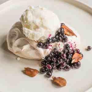 Winter pavlova with meadowsweet ice cream, chokecherry sauce, wild blueberries, butternuts and angelica