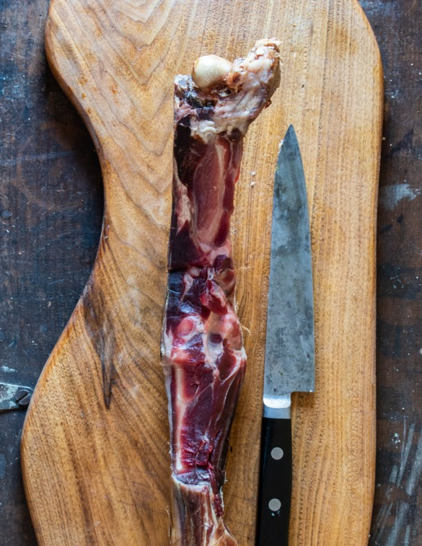 smoked prosciutto bones on a cutting board with carbon steel knife