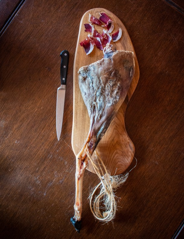 slicing smoked lamb prosciutto whole leg on a cutting board with foot